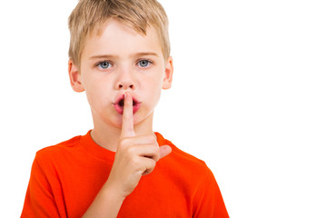 little boy doing silence gesture