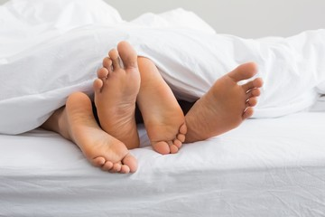 Couples feet sticking out from under duvet