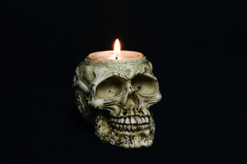 creepy skull candle on black background - half turn
