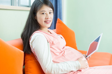 Happy pregnant woman looking at camera, using a digital tablet
