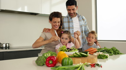 Parents making a salad with their children