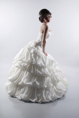 Glamorous bride woman in magnificent wedding dress isolated on g