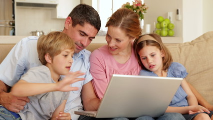 Happy young family sitting on the sofa using laptop together