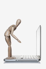 Manikin standing on a laptop computer