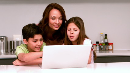 Mother using laptop with her children in kitchen