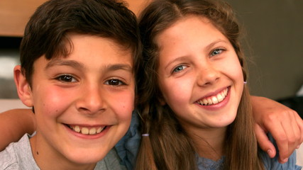 Siblings smiling at camera