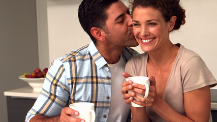 Happy couple having coffee in the kitchen