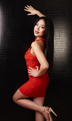 Frau in Rot stützt sich an der Wand