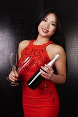 Frau in rot hält Flasche Sekt und Gläser in den Händen