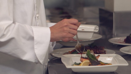 Chef pouring sauce over fish dish