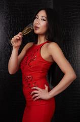 Frau in rot trinkt Sekt