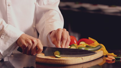 Chef chopping vegetables on wooden board