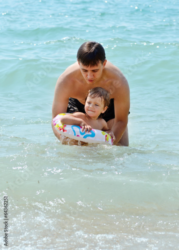 father and toddler daughter in the sea water