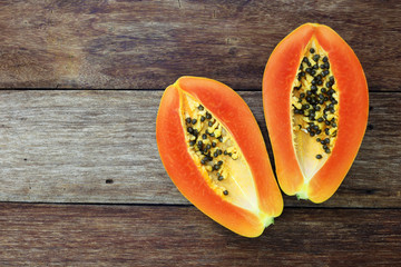 Sliced fresh papaya on wooden background