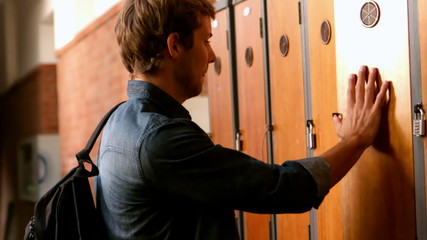 Overwhelmed student leaning against locker