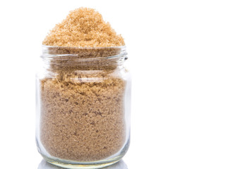 Brown sugar in a glass container over white background
