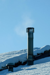 smoking chimney on a snow covered rooftop