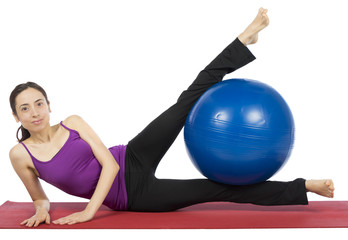 Fitness woman exercising her legs with a pilates ball