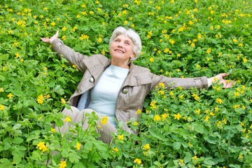 Happy beautiful elderly woman sitting arms outstretched on a gla