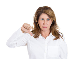 Middle aged woman giving thumbs down gesture, white background