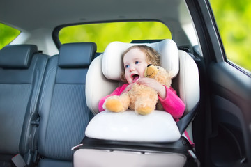 Cute curly toddler girl with a toy bear enjoying a car ride