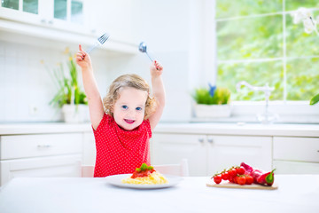 Little toddler girl eating spaghetti in a white kitchen