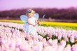 Beautiful toddler girl in fairy costume in a flower field