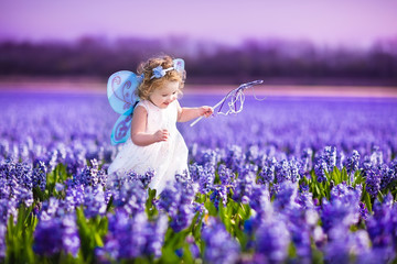 Adorable toddler girl in fairy costume in a flower field