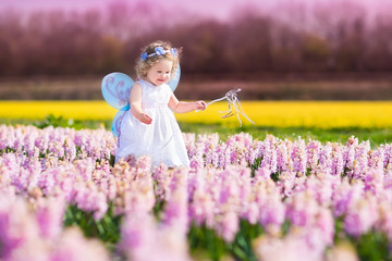 Little toddler girl in fairy costume in a flower field