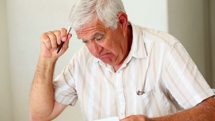 Senior man sitting at table working out bills