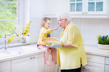 Happy grandmother and little girl baking pie in white kitche