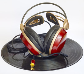 wooden headphones arranged over some old 45 rpm records