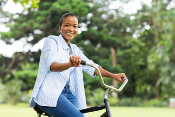 afro american woman riding bicycle in forest
