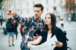 Tourists looking for landmarks in city using map