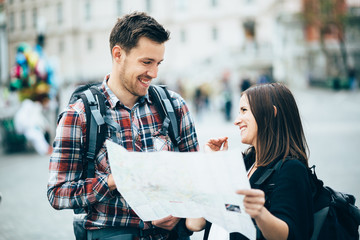 Couple of tourists looking at city map and laughing