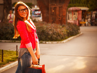 Cool girl walking on the street with shopping bags