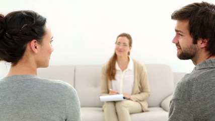 Therapist smiling at reconciled couple