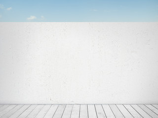 blue sky behind white wall and wooden floor