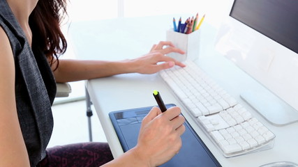 Graphic designer working on digitizer at her desk