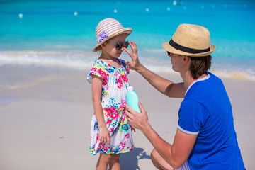 Father apply sunblock cream on his little daughter nose