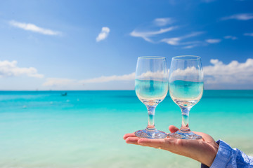 Two clean glasses on background of turquoise sea
