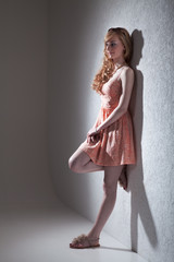 Junge hübsche Frau lehnt an Wand im Fotostudio