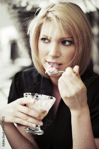 Young woman eating an ice cream at sidewalk cafe