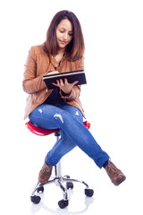 Young casual woman sitting on chair working with a tablet comput