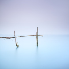 Poles and soft water on foggy landscape. Long exposure.