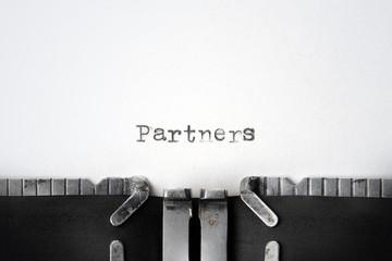 """Partners"" written on an old typewriter"