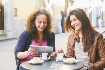 Girls Using Digital Tablet while Having Breakfast