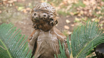Garden statue of a little girl with palm fronds and rain.