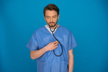 Doctor holding a stethoscope staring at the floor