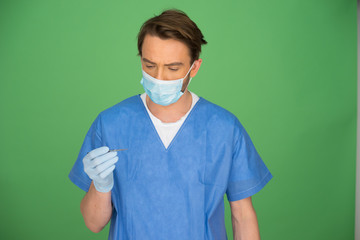 Male doctor or nurse looking at his gloved hand